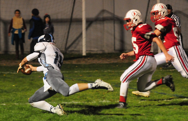 JIM VAIKNORAS/Staff photo Triton's Lewis L'Heureux dives across the goal line as he scores a 2 point conversion at Amesbury Friday night.