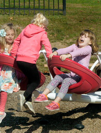 BRYAN EATON/Staff photo. Kindergartners from the Cashman School in Amesbury stopped at the town park for some fun after taking a field trip in the downtown visiting places like the Amesbury Fire Department on Thursday. Kiara Kelcourse, left, and Maya Ecklecamp, both 5, laugh as Chloe Minervini, 6, pulls them down on a see-saw.