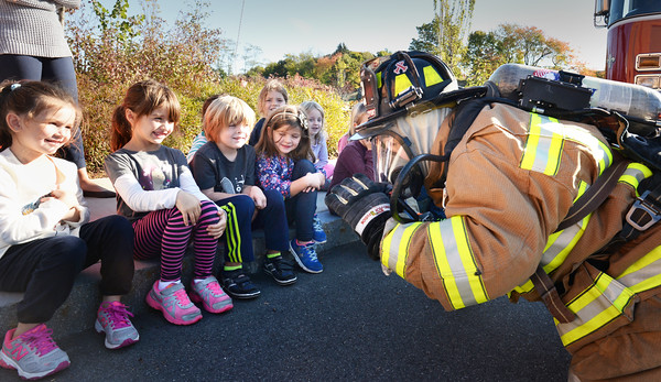 BRYAN EATON/Staff photo. Newburyport's Bresnahan School kindergartners got a visit from Newburyport firefighter Ken Parseghian teaching them about fire safety and prevention. Here he shows off his equipment and how to stay low to the ground to escape from smoke and fire.
