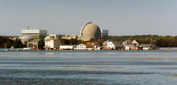 BRYAN EATON/Staff photo. The houses at Cross Beach near Seabrook Harbor, with the nuclear power plant as a backdrop,  look to be surrounded by water during the high tide caused by the Harvest full moon on Monday afternoon. They aren't as there's a causeway about a foot above the water level for residents to access their homes.