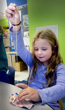 BRYAN EATON/Staff photo. Bianca Turco, 8, pulls the needle high as she works on making a bracelet at the Bresnahan School on Wednesday. Suzy Brown, a volunteer at the Spencer-Peirce-Littlel Farm in Newbury, is teaching the sewing class in the afterschool enrichment program.