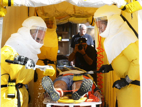 BRYAN EATON/Staff photo. Newburyport firefighter Wendy Kimball, volunteering as one contaminated in an industrial accident, is brushed off from rescue personnel in hazmat suits outside Anna Jaques Hospital.