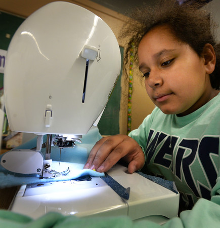 BRYAN EATON/Staff photo. Maya Hayes, 12, works on a fleece jacket in sewing class taught by Judy Gaffney at the Boys and Girls Club on Tuesday afternoon. She's three weeks into the project and is a return participant to the classes as she enjoyed it so much last year.