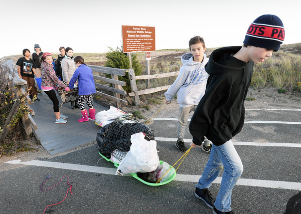 BRYAN EATON/Staff photo. Students remove trash they collected along the beaches at Plum Island with teacher Ellen Link who is on sabbatical.