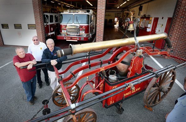 BRYAN EATON/Staff photo. The handtub firefighting apparatus Red Ring built in 1826 sits in front of a modern fire engine given the same name at the Salisbury Fire Department with, from left, retired firefighter Danny Frost, chief Richard Souliotis and call firefighter Keith Sullivan. Sullivan and other firefighters are leading a drive to purchase the piece from Ring's Island resident Frost who bought it back in 1969.