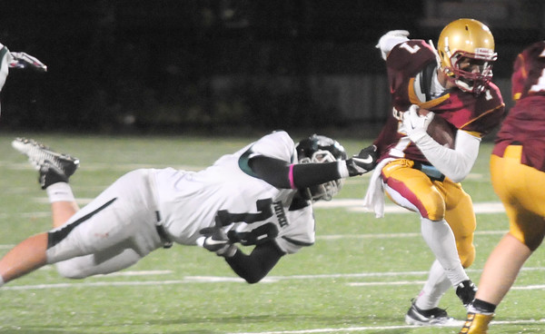 JIM VAIKNORAS/Staff photo Pentucket's Jacob Luke hangs on to Newburyport's Ronnie Mwai at Newburyport Friday night.