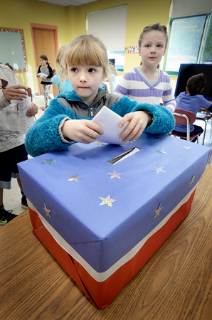 """BRYAN EATON/Staff photo. Ava Valianti, 7, casts her ballot in a mock election Tuesday at Newbury Elementary School where the whole student body participated. When the votes were tallied the Clinton ticket beat the three others garnering 226 out of 408 votes cast. Students were asked to put a word or two on a card after they voted asking what qualities a leader should have resulting in """"helps others,"""" """"brave,"""" """"help and kindness"""" and one that read """"not Hillary."""""""