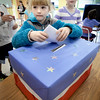 "BRYAN EATON/Staff photo. Ava Valianti, 7, casts her ballot in a mock election Tuesday at Newbury Elementary School where the whole student body participated. When the votes were tallied the Clinton ticket beat the three others garnering 226 out of 408 votes cast. Students were asked to put a word or two on a card after they voted asking what qualities a leader should have resulting in ""helps others,"" ""brave,"" ""help and kindness"" and one that read ""not Hillary."""