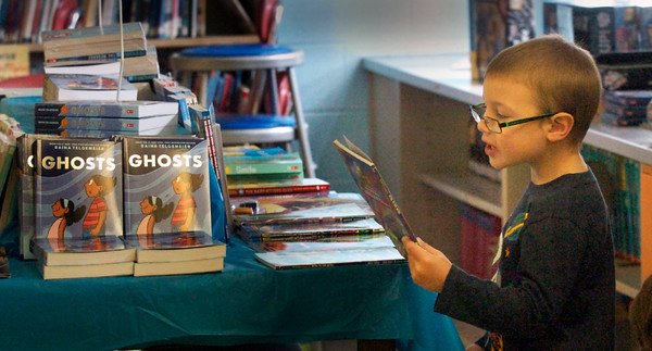 BRYAN EATON/Staff photo. Cameron Hughes, 5, checks out some scary books especially ones in the Zombie series at Amesbury Elementary School. He wad perusing tomes at the Book Fair which raises money for the school's library.