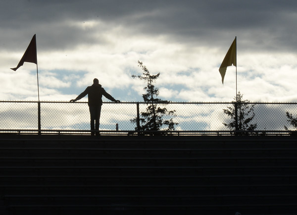 BRYAN EATON/Staff photo. A spectator to the Newburyport girls soccer game with Masconomet watches from the top of the bleachers at World War Memorial Stadium on Wednesday afternoon under dark clouds. More clouds are moving in today with rain in the forecast.