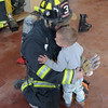 JIM VAIKNORAS/Staff photo Landen Blades, 2, gives Salisbury Firefighter Mike Reusch a hug after Reusch's demostrated putting on his turnout gear at the Salisbury Fire Station Open house