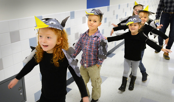"""BRYAN EATON/Staff photo. Bresnahan School pre-kindergartners dressed as crows raise their """"wings' during an Animal Parade through the hallways on Thursday afternoon. They had finished a unit studying different animals found on farms which they visited earlier in the season."""