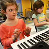 BRYAN EATON/Staff photo. Fingers at the ready Hannah Weetman, left, listens to piano instructor Alia Mavroforos with Ava Ranney, both 6. They were in beginner piano class at the Bresnahan School's Afterschool Enrichment program on Tuesday afternoon.