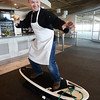 RYAN EATON/Staff photo. Bartender Jim Shalkoski tries out a Pilates surfboard to be auctioned.