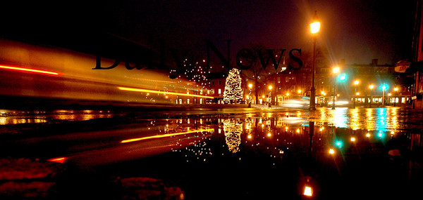 Newburyport: Cars stream by a post holiday scene in Market Square in Newburyport. The lights are reflected in a puddle on Merrimack Street caused by Monday's rain.<br /> Photo by Jim Vaiknoras/Newburyport Daily News. Monday, January 15, 2007