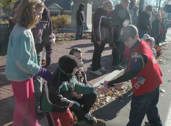Amesbury:Amesbury Boy Scout Jason Gagnon hands out flags to those lining School Street during yesterday's Veterans Day parade in downtown Amesbury.<br /> Dave Rogers/Staff photo
