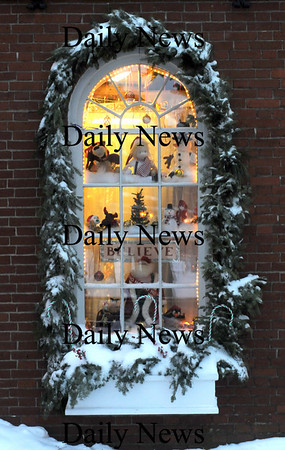 "Newburyport: ""In the air there's a feeling of Christmas"" The holday decorations in the window of the Dragon's Nest toy store in Market Square is framed by snow and a graland of evergreens.photo by Jim Vaiknoras/Newburyport Daily News.Sunday December 21, 2008"