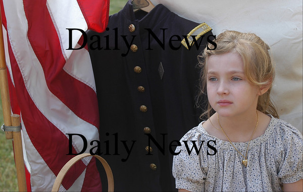 Amesbury: <br /> Joy Jancewicz, 6, of Amesbury, sits beside a union army uniform at the Civil War encampment at the Bartlett Museum Saturday. On friday she helped her father Paul make hardtack, so people visiting the encampment could see how the soldiers eat during the war.<br /> Photo by Jim Vaiknoras/Newburyport Daily News. Sunday, July 31, 2005