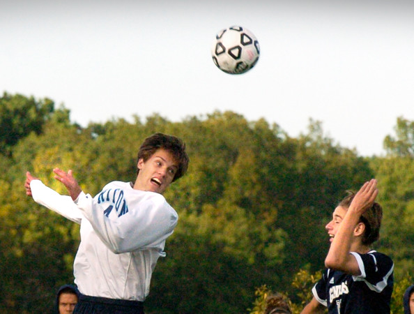 BRYAN EATON/Staff photo. Triton's Ross Lojek heads the ball in his team's direction.