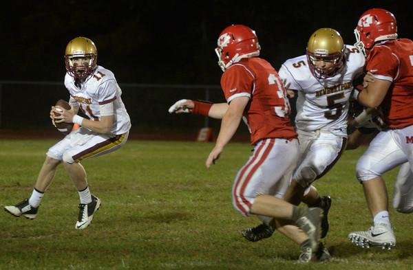 BRYAN EATON/Staff Photo. Newburyport quarterback Robert Shay looks for an open receiver as James Gallo fends off Masco players.