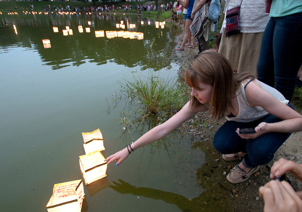 Newburyport:Sarah Collins puts a lantern  in the frog pond at the Bartlet Mall in Newburyport Sunday night as part of the third annual  Overian Cancer Awareness Lantern Festival, over 300 people attended the event. Jim Vaiknoras/staff photo