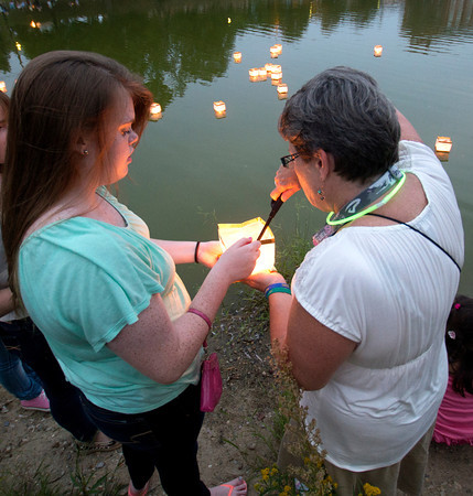 Newburyport: Volunteer Maryellen Lawler lights the candle inside Kristen Siebrt's lantern at the Bartlet Mall in Newburyport Sunday night as part of the third annual  Overian Cancer Awareness Lantern Festival. Jim Vaiknoras/staff photo