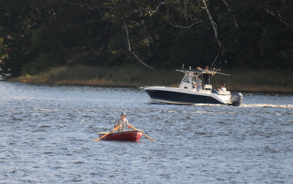 Amesbury: A row boat makes it's way up the Merrimack River Sunday as a fishing boat heads down river near Point Shore in Amesbury. Jim Vaiknoras/staff photo