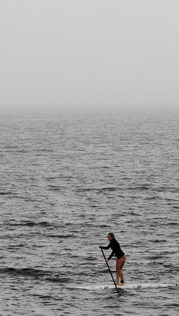 Newbury: A stand up paddle boarder glides along Plum Island Beach as the fog and rain moves in Sunday afternoon. Jim Vaiknoras/staff photo