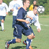 Byfield: Triton's Josh Brown chases the ball with  Hamilton-Wenham's John Dyer during their game at Triton Friday afternoon. Jim Vaiknoras/staff photo