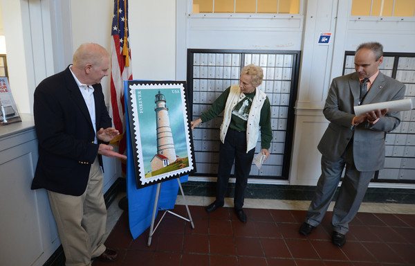 Newburyport:Reired Admiral Daniel May , President of the Friends of the Plum Island Lighthouse Barbara Keazer, and Postmaster of Newburyport Paul Bolas unvail a poster of the Boston Harbor Lighthouse at the Newburyport Post Office Saturday. The event was a celebration of the New England Coastal Lighthouse Forever Stamps which has almost sold out of their 82 million print run. Jim Vaiknoras/staff photo