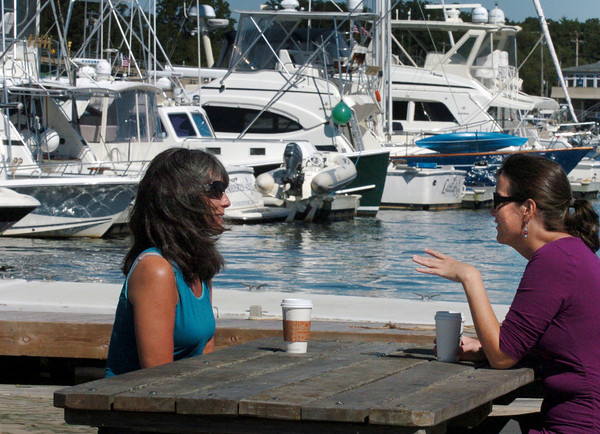 Newburyport: Heather Schwab, left, and Jennifer Allard, both of Newburyport, enjoy coffee and conversation under a sunny sky, though slightly windy, at Somerby's Landing on the Newburyport waterfront Wednesday. Nice weather is expected to continue into the weekend with showers possible late Sunday. Bryan Eaton/Staff Photo