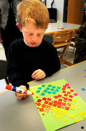 Salisbury: Jacob Mies, 6, glues on pieces of square paper as he learns about mosaic shapes and colors in Amy Merluzzi's art class at Salisbury Elementary School on Tuesday afternoon. Bryan Eaton/Staff Photo