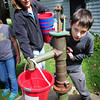 Newbury: Peg Foley of Spencer-Peirce-Little Farm in Newbury looks on as Upper Molin School student Owen Keough, 9, uses his strength to pump water from the well at the historical site. The students were learning about immigration and early times in America. Bryan Eaton/Staff Photo