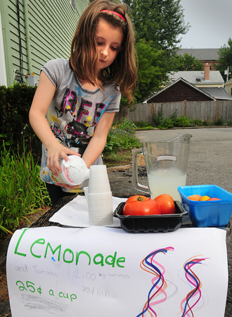 Newburyport: Cassidy  Anderson, pours lemonade at her stand in Newburyport's South End on Tuesday afternoon. The soon-to-be nine year-old also was selling tomatoes from her garden. Bryan Eaton/Staff Photo