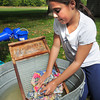 Newbury: Sophia Gioldasis, 10, uses a washboard to clean clothes on a field trip at the Spencer-Peirce-Little Farm in Newbury on Wednesday. The children then went to the Audubon Joppa Flats Education Center as they learned about immigration and adoption tied into their unit on history. Bryan Eaton/Staff Photo