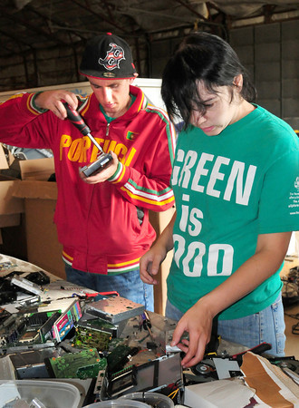 Newburyport: Ben Bunnell, Pauline Tessier, and Drew Pinto, out of view, takes out recyclable components from computer hard drives and other electronics at the Crow Lane Transfer Station. Bryan Eaton/Staff Photo