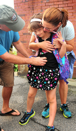 Amesbury: Hannah Nahas, 7, gets a warm send off as she heads into Amesbury Elementary School on Tuesday for the first day of classes from her parents, Jeff and Kellyn. Triton District Schools also started. Bryan Eaton/Staff Photo