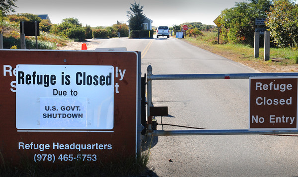 Newbury: A Parker River National Wildlife Refuge employee drives past the pass hut after opening the gate and driving through yesterday morning. A half dozen cars were waiting to get in but drove off after seeing the sign posted. Bryan Eaton/Staff Photo