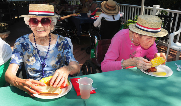 """Newburyport: Marjorie McVeigh, left, and Helena Earle dine on corn, hot dogs, grilled chicken and watermelon at a cookout Wednesday at the Brigham Manor in Newburyport. They have a cookout for the residents every two weeks starting in June with this one being their """"swan song"""" for the year. Bryan Eaton/Staff Photo"""