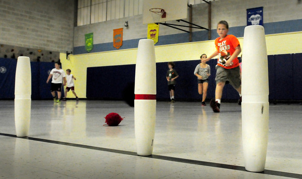 """Amesbury: Children throw sacks at bowling pins in a game of """"Battleship"""" in Margaret Welch's physical education class at Amesbury Elementary School on Thursday. One team had a red stripe on their pins, the other, none and whatever team got them all down first, one. Bryan Eaton/Staff Photo"""