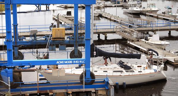 Salisbury: Woody Delgado of Newburyport motors his 38' sailboat under a lift to be taken out of the Merrimack River for the season at Bridge Marina in Salisbury. Bryan Eaton/Staff Photo