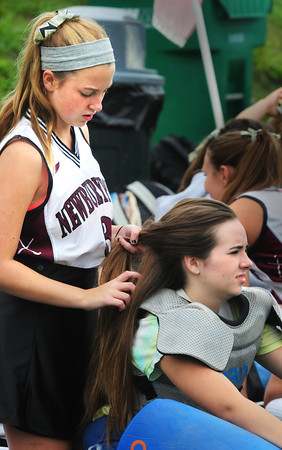 Newburyport: Hannah Rikeman, left, braids teammate Newburyport High junior varsity goalie Sam Degou's hair Tuesday. They were waiting for the varsity to finish their game against Saugus at Amesbury Sports Park. Bryan Eaton/Staff Photo