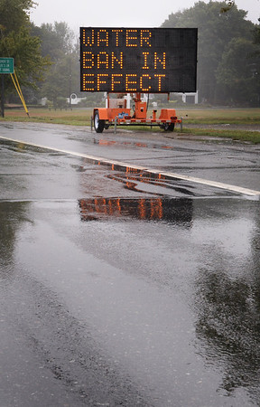BRYAN EATON/Staff photo. A water ban sign at Newbury's Upper Green is if reflected on a rain-covered High Road yesterday morning. The rain from the remnants of Hurrican Hermine was welcome, but not enough to end the severe drought.