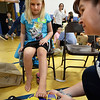 "BRYAN EATON/Staff photo. Nikki Welch, 8, gets her foot size taken at Seabrook Middle School by Traci Barnum, an employee of Timberland. The company, known for their community service, gave out 750 pairs of footwear in the ""Shoe Fit Footprint Fair."""