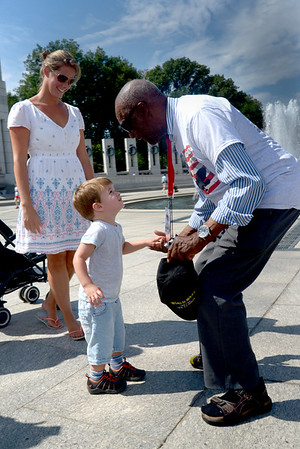 JIM VAIKNORAS/Staff photo Lt.Col. USAF (ret) Enoch Woodhouse, who flew during the war with the Tuskegee Airman is greeted by a young British boy and his family at the World War 2 Memorial in Washington DC.