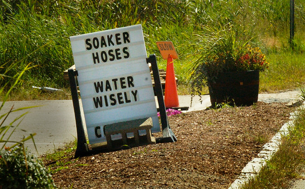 BRYAN EATON/Staff photo. A sign at Harbor Gardens in Salisbury sells water efficient hoses and reminds people to conserve water