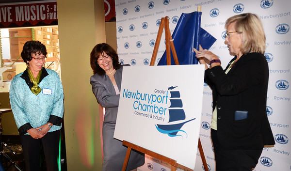 BRYAN EATON/Staff photo. Newburyport Chamber of Commerce and Industry board of directors chair Grace Connolly, center, and president Ann Ormond unveil their new logo designed by Rose Russo, left, at the Newburyport Brewing Company on Tuesday night.