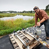 BRYAN EATON/Staff photo. Grigore Chitas of Cider Hill Farm in Amesbury primes one of two new pumps installed to take water from the pond in rear to irrigate vegetables and apple trees.