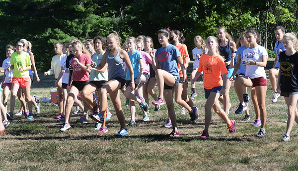 BRYAN EATON/Staff photo. The Newburyport High girls cross country team do knee lifts to warm up.