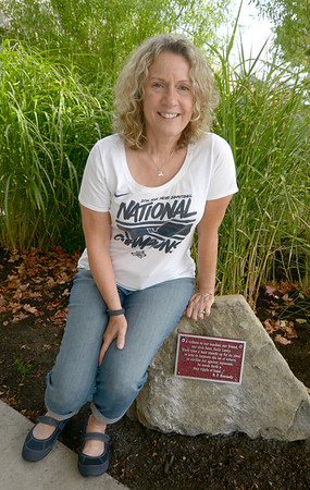 """JIM VAIKNORAS/Staff photo Sally Leety sits on a stone baring a plaque dedicated to her at the entrance way to the Nock Middle School. Leety is retiring after 34 years teaching social studies, the plaque reads """" A tribute to our teacher, our civic hero, Sally Leety. """"Each time a man stands up for an ideal, or acts to improve the lot of others, or strikes out against injustice, he sends forth a tiny ripple of hope""""<br /> R F Kennedy."""